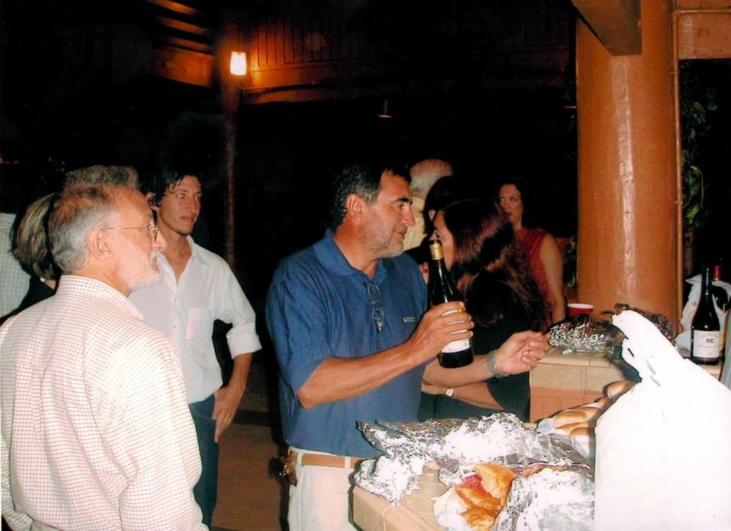 Mi papa intenta abrir un vino mientras Max y su papa observan la maniobra