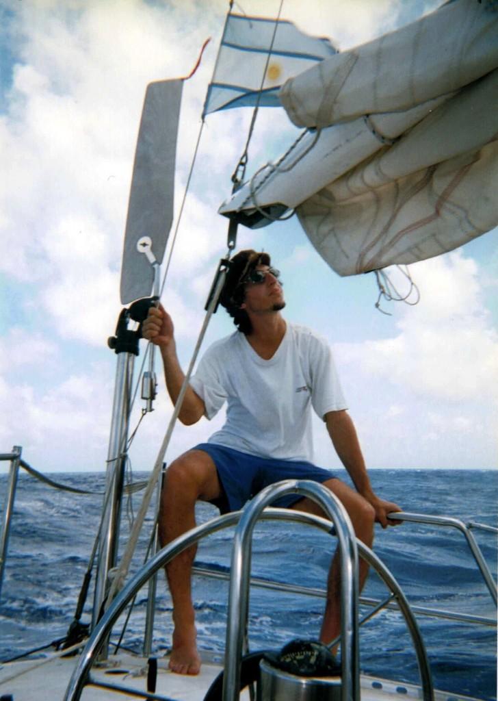 Max recuperado del mareo junto a la bandera argentina y el timon de viento.